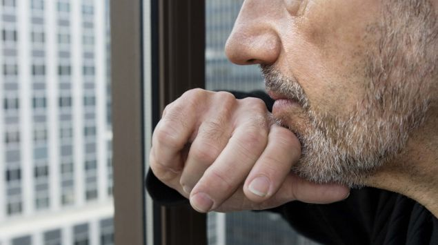Ein Mann schaut nachdenklich aus dem Fenster eines Hochhauses
