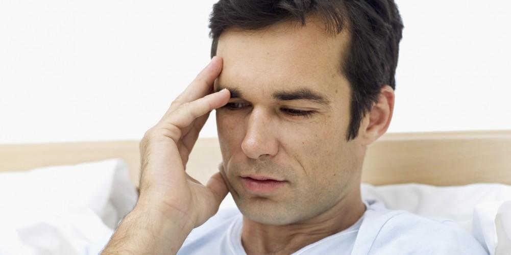 Ein Mann sitzt im Bett und hält sich die Hand an die Stirn.