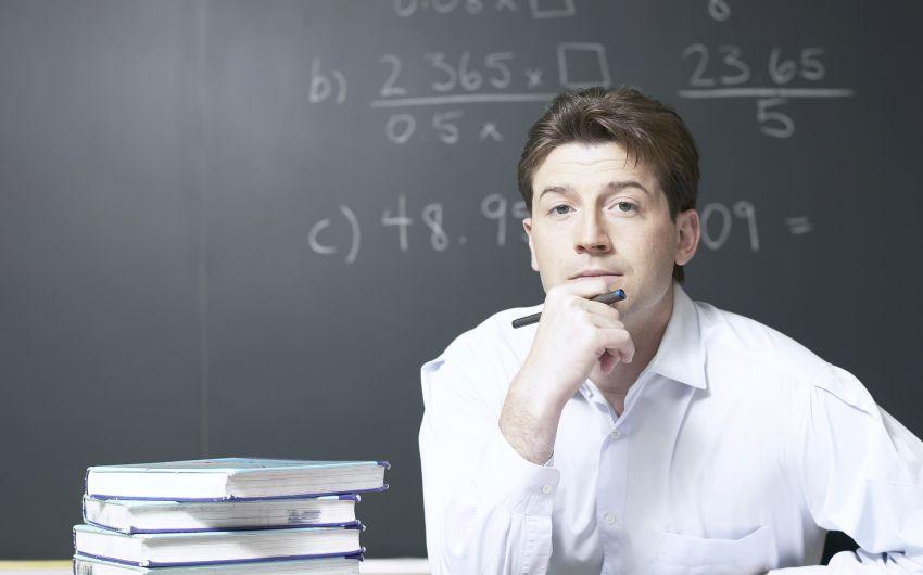 Ein junger Mann sitzt mit Büchern am Tisch, auf der Tafel hinter ihm mathematische Formeln.