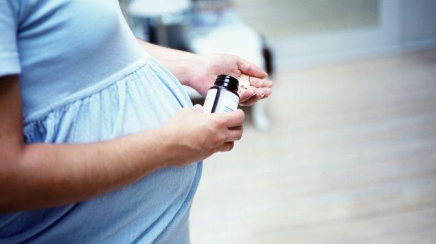 Das Bild zeigt eine Schwangere mit Tabletten.