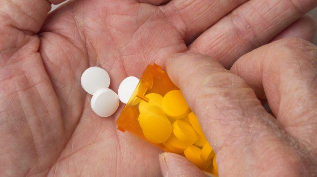 Jemand hält ein Röhrchen mit Tabletten in der Hand.