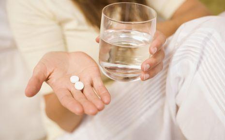 Kopfschmerzen durch Schmerzmittel: Man sieht eine Hand mit Tabletten und ein Glas Wasser.