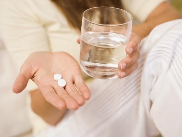 Lungenentzündung: Man sieht eine Hand mit Tabletten und ein Glas Wasser.