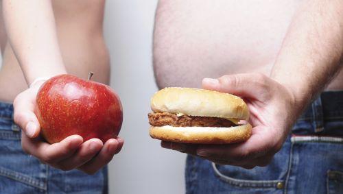Das Bidl zeigt eine Frau, die einen Apfel hält und einen Mann, der einen Burger hält.