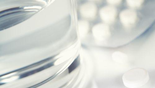 Das Bild zeigt mehrere Tabletten neben einem Glas mit Wasser.