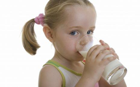 Ein Mädchen trinkt ein Glas Milch.