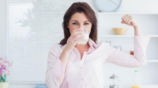 Eine Frau trinkt ein Glas Milch und spannt ihren Bizeps an.