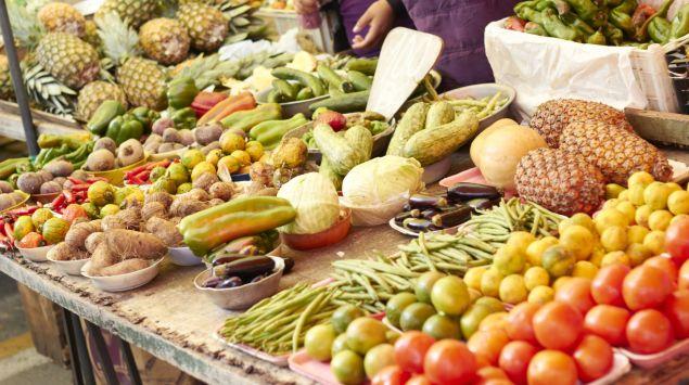 Das Bild zeigt einen Marktstand mit Obst und Gemüse.