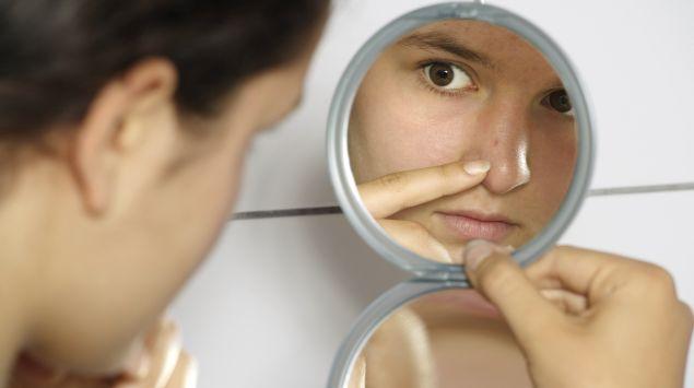 Das Bild zeigt ein Mädchen, das sich im Spiegel einen Mitesser ansieht.