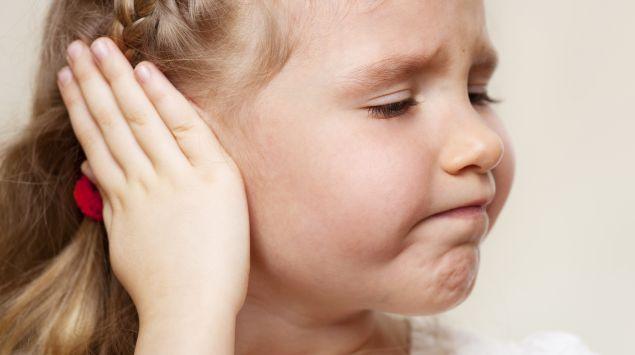 Das Bild zeigt ein Mädchen, dass sich die Hand auf das Ohr legt.