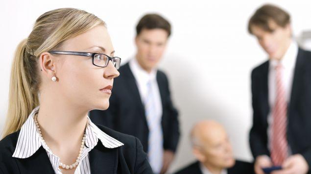 Das Bild zeigt eine Geschäftsfrau vor drei männlichen Kollegen.