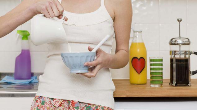Das Bild zeigt eine Frau, die Milch in eine Schüssel giesst.