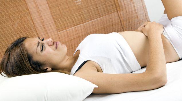 Das Bild zeigt eine Frau, die ihre Hände auf den Bauch gelegt hat.