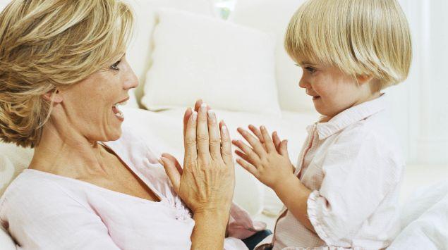 Das Bild zeigt eine Frau, die mit einem kleinen Jungen spielt.