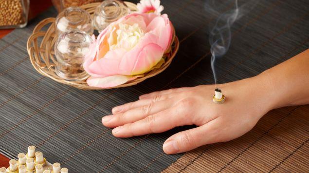 Moxa-Therapie auf einer Hand.
