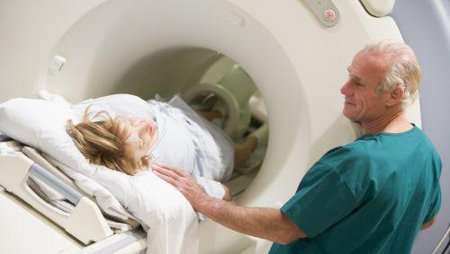 Das Bild zeigt wie eine Patientin von einem Pfleger ins MRT geschoben wird.