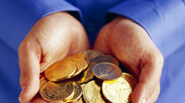 Jemand hält Münzen in seinen Händen.