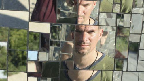 Das Gesicht eines Mannes in verschiedenen Spiegelstücken.