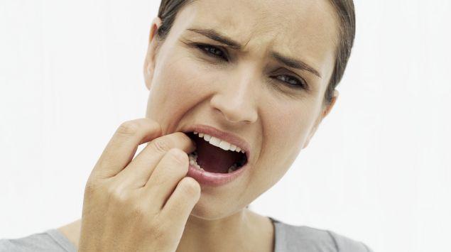 Das Bild zeigt eine Frau, die Schmerzen im Mund hat.