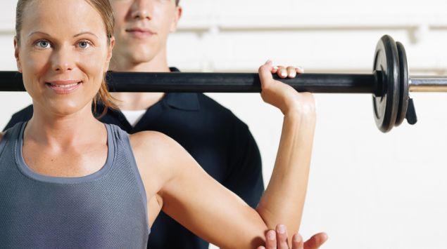 Eine Frau macht eine Übung an einer Stange, hinter ihr ein Mann, der assistiert.