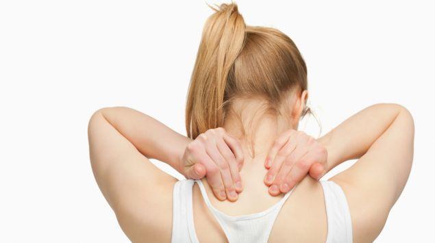 Eine Frau fasst sich mit den Händen in den Nackenbereich.