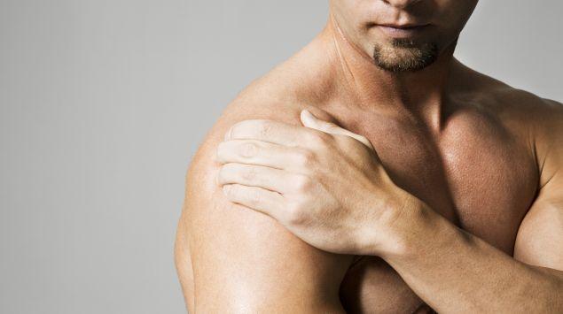 Das Bild zeigt einen Mann mit freiem Oberkörper, der sich an die Schulter greift.