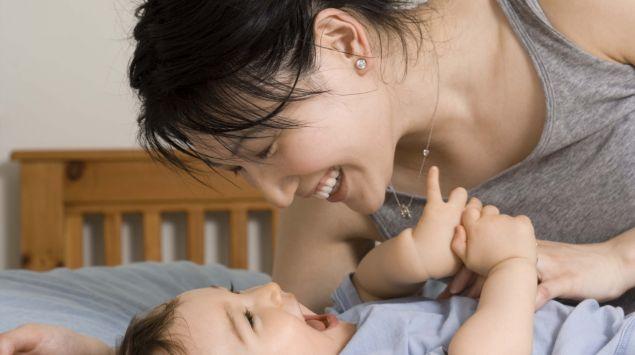 Das Bild zeigt eine Mutter, die mit Ihrem kleinen Kind spielt.