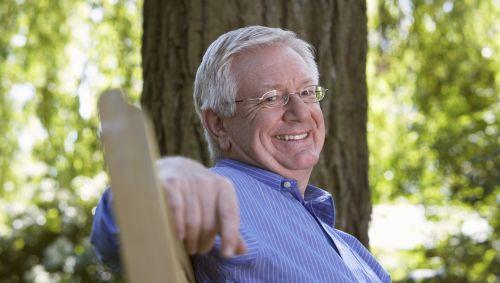 Ein älterer, lächelnder Mann sitzt draußen auf einer Bank.