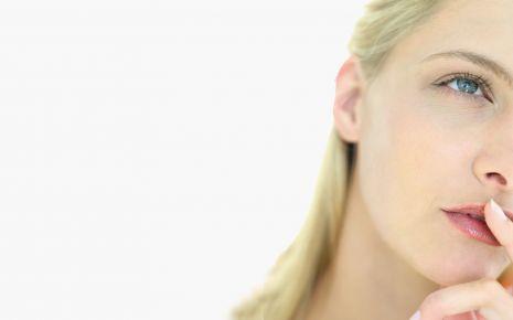 Man sieht eine blonde Frau in Denkerpose.