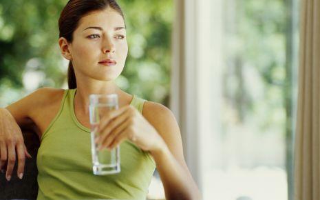 Man sieht eine nachdenkliche Frau, die ein Glas Wasser trinkt.