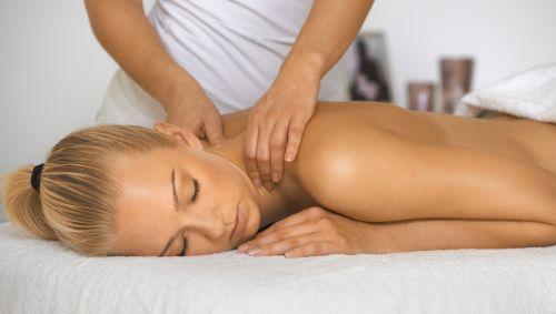 Das Bild zeigt eine Frau mit freiem Oberkörper, die massiert wird am Nacken.