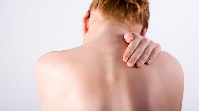 Das Bild zeigt eine Frau mit nacktem Oberkörper von hinten, die sich an den Nacken fasst.