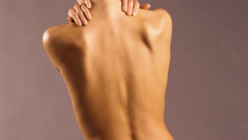 Eine nackte Frau hält sich die Händei m Nackenbereich.