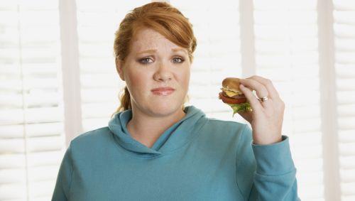 Das BIld zeigt eine übergewichtige Frau, die einen Burger in der Hand hält.