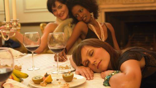 Das Bild zeigt eine Frau, die den Kopf auf den Esstisch gelegt hat und schläft.