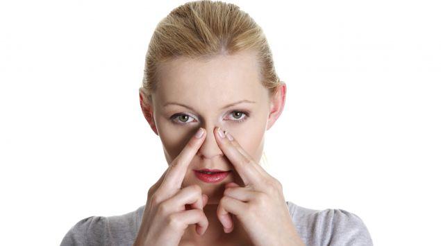 Das Bild zeigt eine Frau die sich an die Nase fasst.