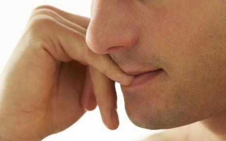 Ein Mann kaut an seinen Fingernägeln.