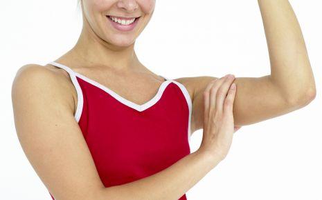 Das Bild zeigt eine Frau, die ihren Oberarmmuskel befühlt.