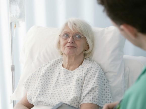 Das Bild zeigt eine ältere Frau im Krankenbett.