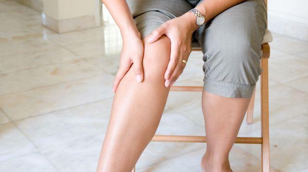 Das Bild zeigt eine Frau, die auf einem Stul sitzt und sich ihr Knie hält.