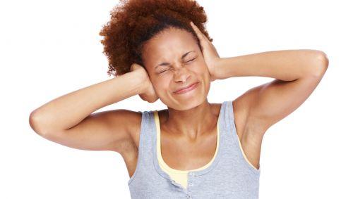 Das Bild zeigt eine Frau, die sich die Ohren zuhält.
