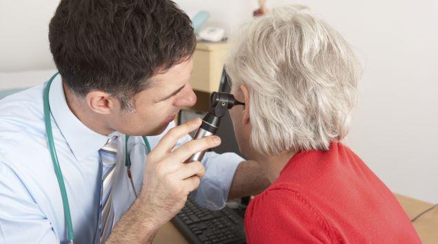 Das Bild zeigt einen Arzt, der einer Patientin ins Ohr schaut.