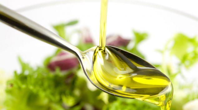 Man sieht einen Löffel mit Olivenöl.