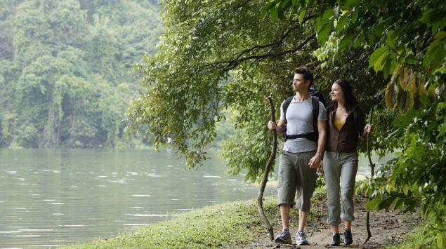 Das Bild zeigt zwei Personen an einem Fluss entlang wandern.