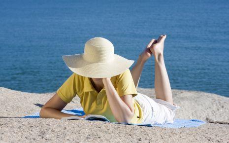 Das Bild zeigt eine Frau mit Sonnenhut am Strand liegend.