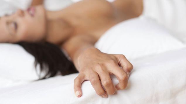 Das Bild zeigt eine nackte Frau im Bett.