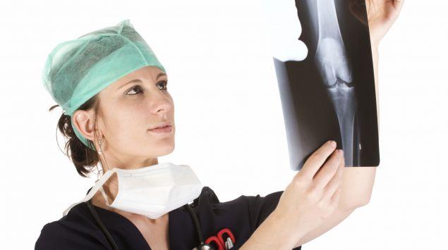 Das Bild zeigt eine Ärztin, die sich ein Röntgenbild ansieht.