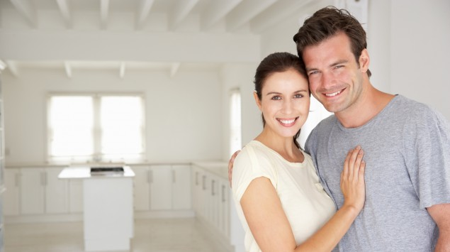 Paar steht in der Küche und schaut lächelnd in die Kamera.