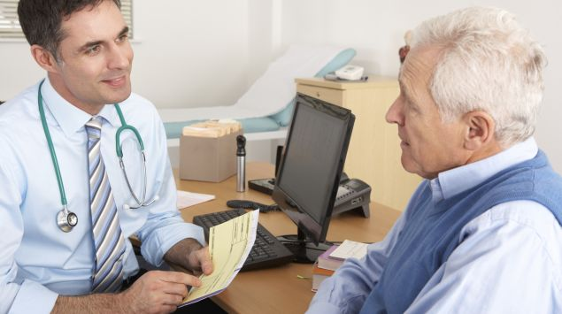 Ein Arzt im Gespräch mit einem älteren Patienten.