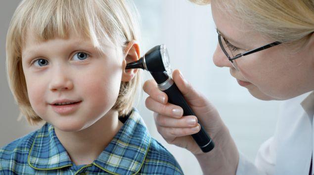 Das Bild zeigt eine Ärztin, die das Ohr eines Kindes untersucht.